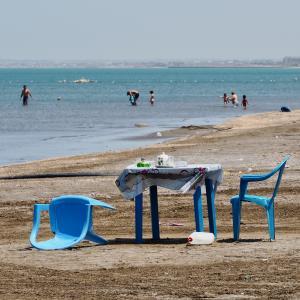 Plastiktisch und -stühle am Strand